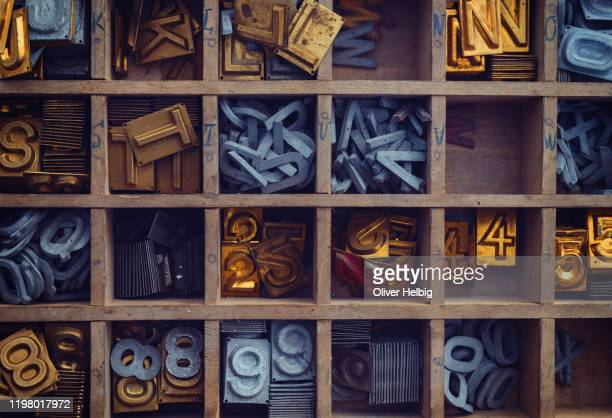 wooden case with different antique metal letters and numbers - brass stock pictures, royalty-free photos & images