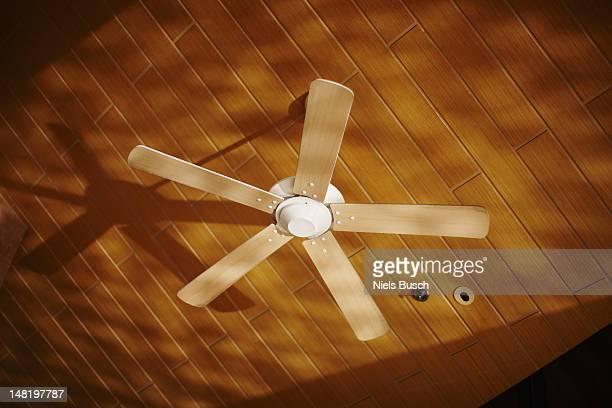 Wooden ceiling fan casting shadows