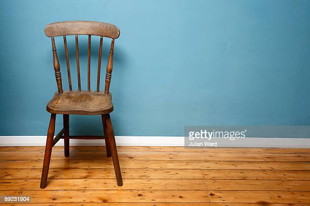 wooden chair against a blue wall in an empty room - cadeira - fotografias e filmes do acervo