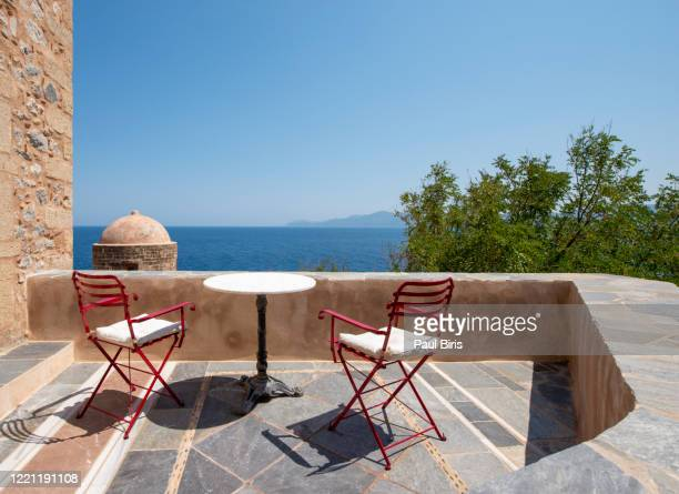 wooden chair and table on balcony in old ancient village monemvasia in peloponnese, greece - europa meridionale foto e immagini stock