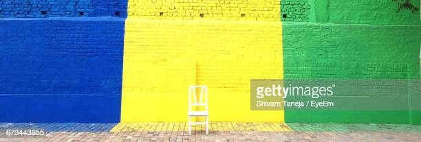 Wooden Chair On Footpath Against Multi Colored Brick Wall