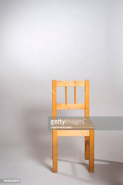 Sedia in legno su sfondo grigio.