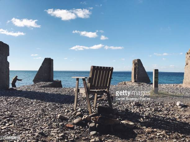 Wooden Chair Over Rocks Against Sky