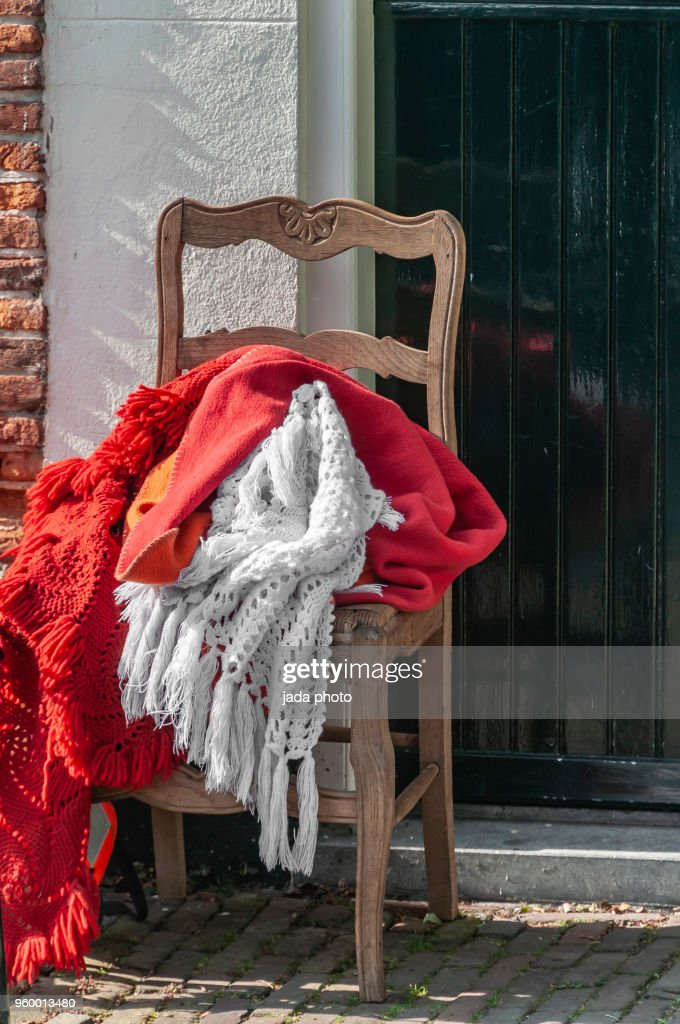wooden chair with various colours of blankets : Stock-Foto
