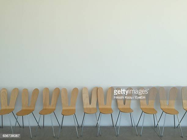 Wooden Chairs Arranged Against Wall