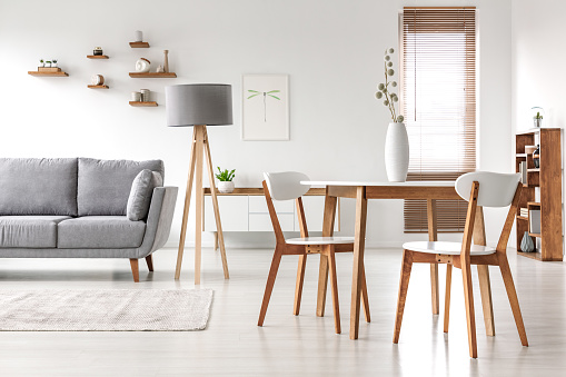 Wooden chairs at table in bright open space interior with lamp next to grey couch. Real photo 968086564