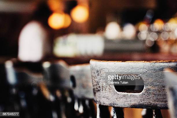 Wooden chairs in row in bar