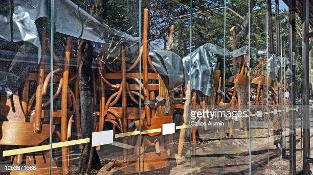 wooden chairs upside down on their tables of a closed bar and restaurant, viewed from the street through its window - carlos alkmin stock pictures, royalty-free photos & images