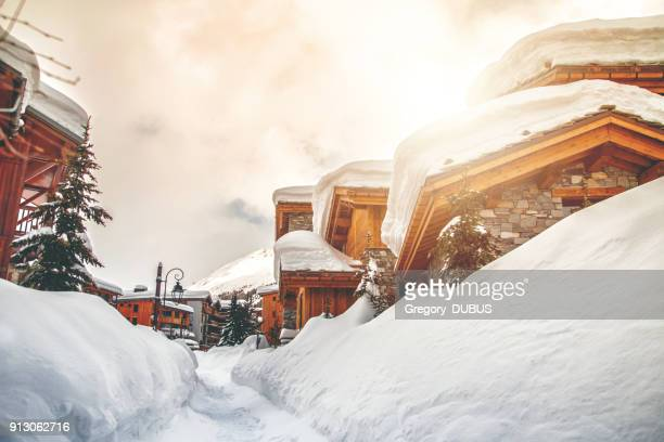 wooden chalet and snow footpath in french ski resort of val d'isere - european alps stock pictures, royalty-free photos & images