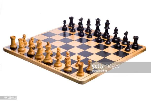 A wooden chessboard set up prior to play