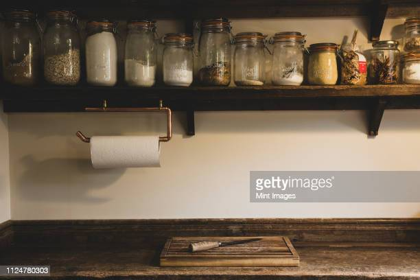 wooden chopping board and knife on vintage wooden kitchen cupboard, row of glass jars with cooking ingredients on a wooden shelf. - kitchen paper stock pictures, royalty-free photos & images