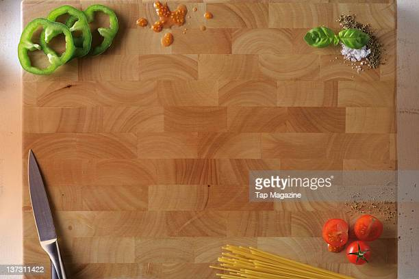 A wooden chopping board and knife with vegetables spaghetti herbs and spices October 29 2010