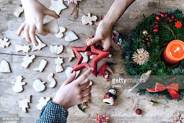 wooden christmas table with hands holding cookies and decoration