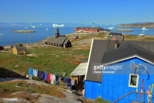 a wooden church and colorful wooden houses situated at the sea with icebergs in the distance - rainer grosskopf stock pictures, royalty-free photos & images