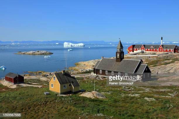 a wooden church and colorful wooden houses situated at the sea with icebergs in the distance - rainer grosskopf stockfoto's en -beelden