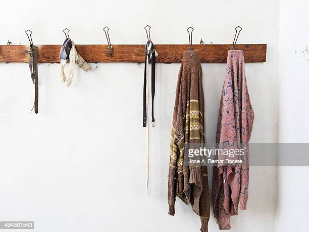Wooden coat rack wall hanging with old clothes