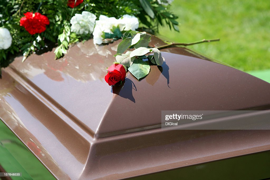 Wooden color casket with flowers and a rose on top : Stock Photo