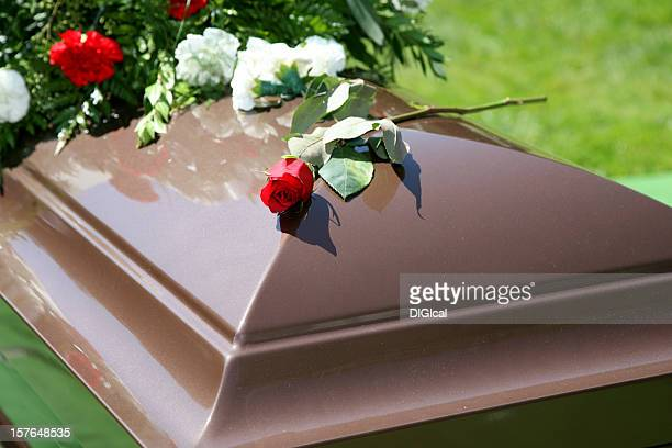 wooden color casket with flowers and a rose on top - funeral stock pictures, royalty-free photos & images