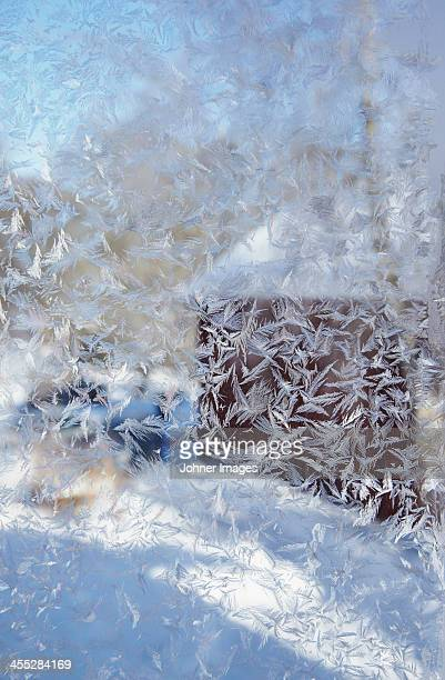 Wooden cottage at winter view through frosted window