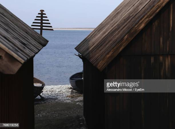 wooden cottages at beach against sky - alessandro miccoli stock pictures, royalty-free photos & images