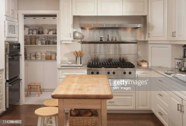 wooden counter and stove in modern kitchen - kitchen stock pictures, royalty-free photos & images