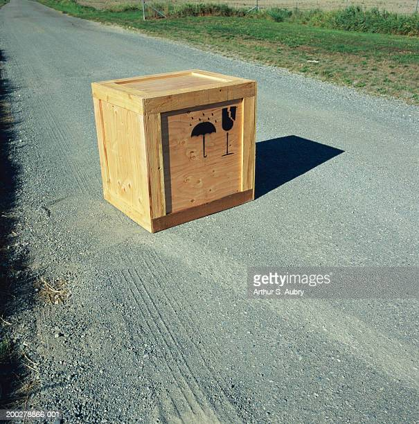 Wooden crate with 'Fragile' and 'Do not get wet' symbols on road