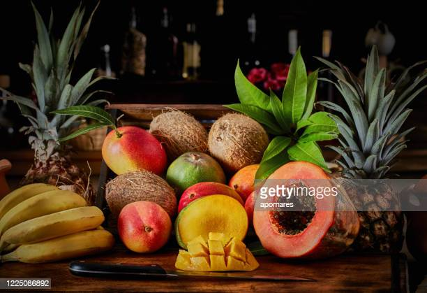 caisses en bois avec des fruits tropicaux assortis dans la cuisine rustique. éclairage naturel - fruit exotique photos et images de collection