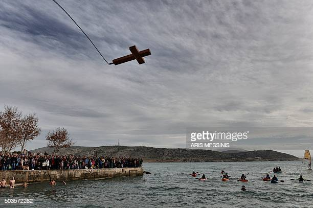 A wooden cross is thrown in the sea during the blessing of the waterceremony marking the orthodox Epiphany Day in a southern suburb of Athens on...