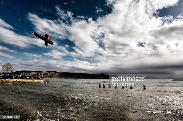 TOPSHOT A wooden cross is thrown to the sea during the blessing of the water ceremony marking the orthodox Epiphany Day in a southern suburb of...