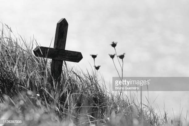 wooden cross on the edge of a cliff - tod stock-fotos und bilder