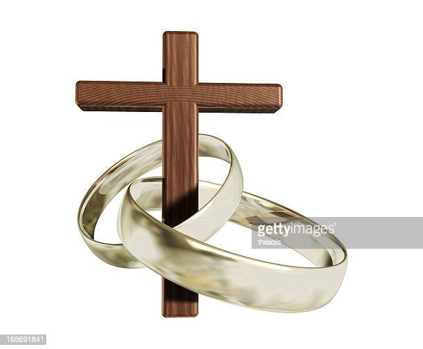 Wooden cross threaded through  two silver wedding rings