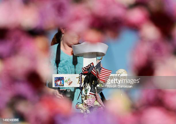 A wooden cross with the name and sailor's cap of shooting victim John Larimer the Navy intelligence officer from Crystal Lake Illinois is viewd...