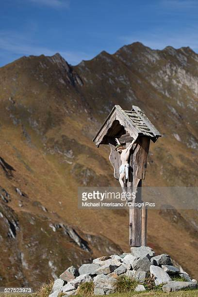 Wooden crucifix memorial on grassy slope with mountain range and blue sky in the background