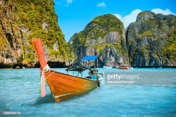 cortador de madera longboat amarrado en ko phi phi le island, tailandia - exotismo fotografías e imágenes de stock