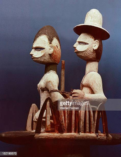 Wooden dance headdress showing a slave trader wearing a European hat with his woman captive Nigeria Igbo 20th c