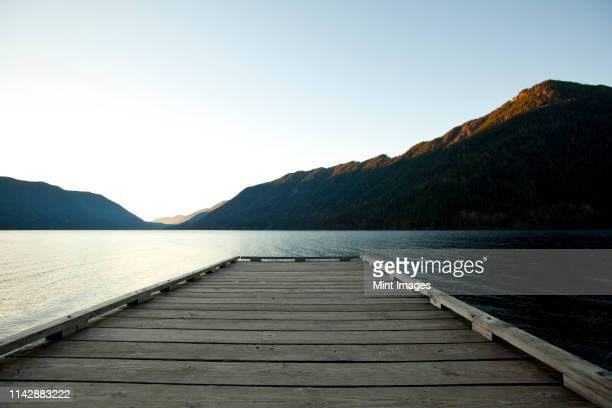 wooden deck at lake under blue sky - quayside stock pictures, royalty-free photos & images