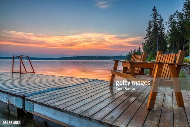 wooden deck chairs on jetty by clear lake at sunrise, riding mountain national park, manitoba, canada - molo foto e immagini stock