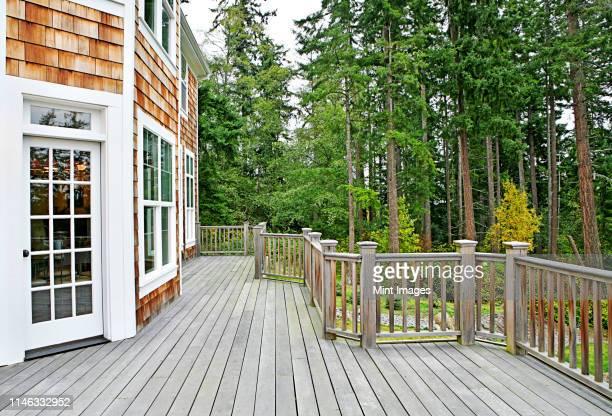 wooden deck on house near forest - ウッドデッキ ストックフォトと画像