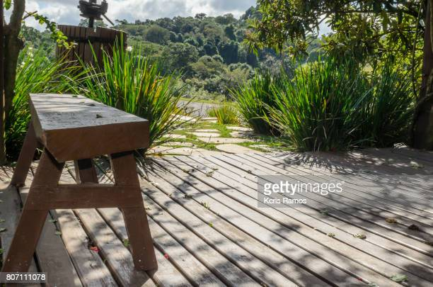 Wooden deck with wooden bench and plants in sunny day horizontal