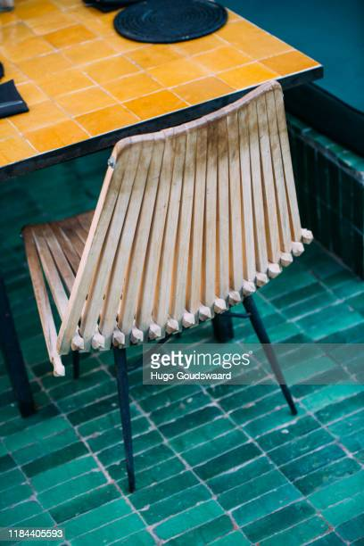 wooden design chair in a hotel like surrounding on a green tile floor - courtyard stock photos and pictures