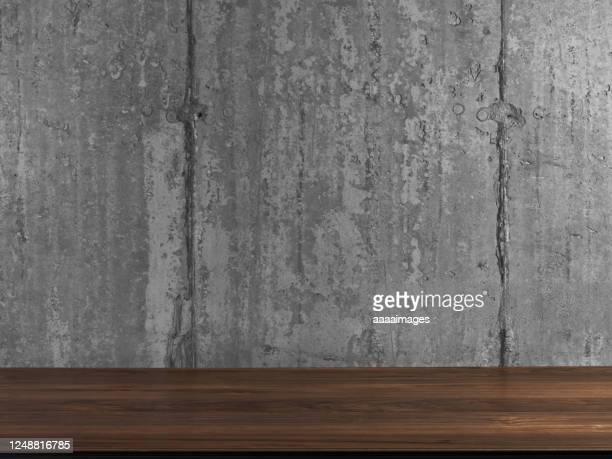 wooden desk against clean concrete wall - visão frontal imagens e fotografias de stock