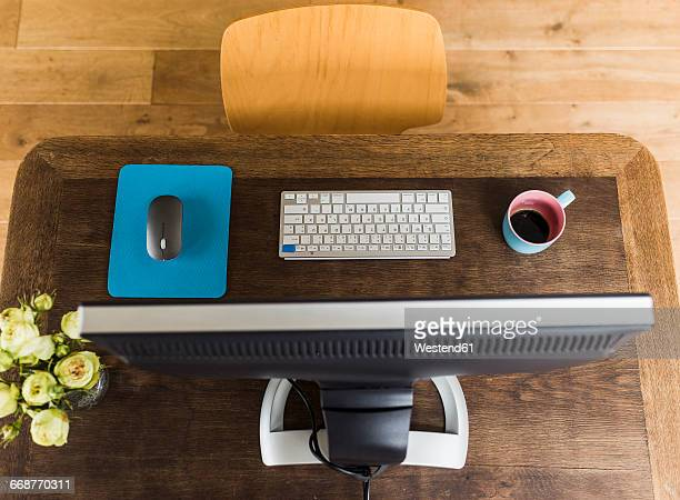Wooden desk with keyboard, coffee cup and mouse