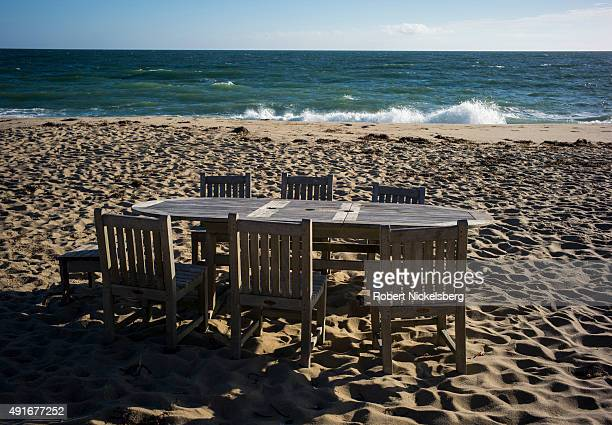 Wooden dining table and chairs sits on the beach September 23, 2015 on Nantucket Island in Wauwinet, Massachusetts. Sea levels continue to rise at...