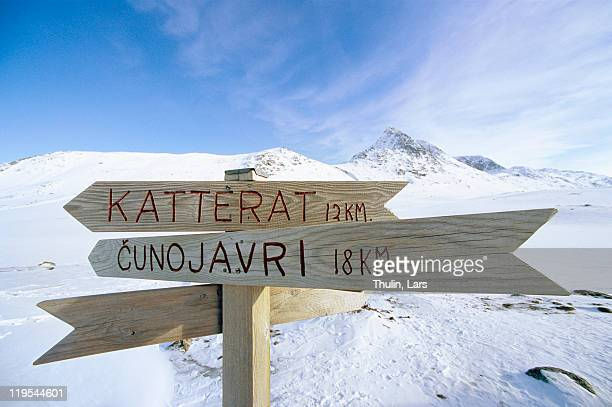 Wooden direction sign in winter mountain scenery
