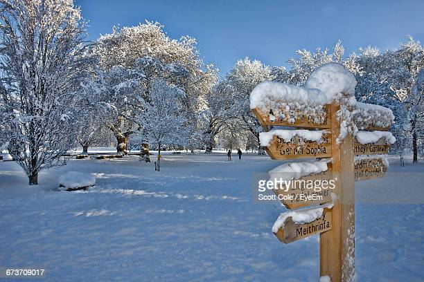 Wooden Directional Sign On Snow Covered Field