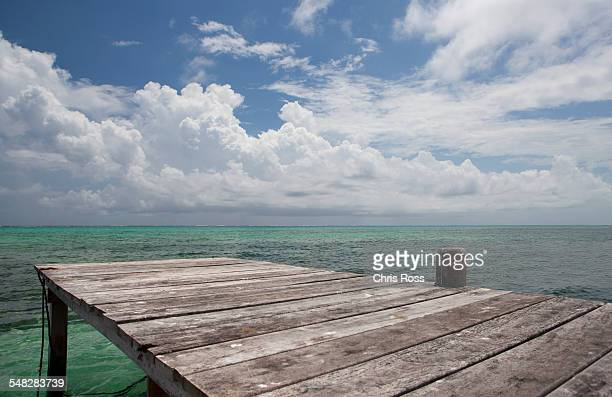 wooden dock stretches out to blue green ocean water with puffy clouds in the sky