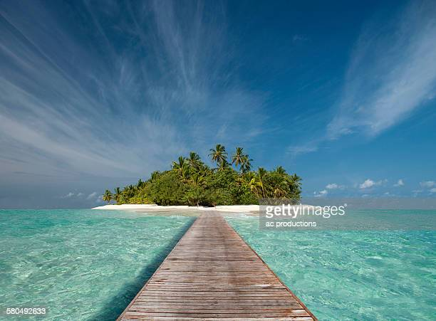 Wooden dock walkway to tropical island