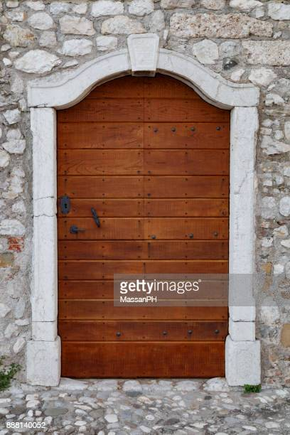 Wooden door and stone wall of the ancient mill of Ospedaletto in Gemona