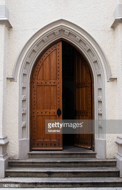 wooden door half open on a medieval style building entrance - church stock pictures, royalty-free photos & images