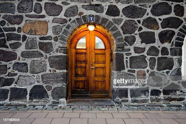 Wooden door in illuminated doorway, set within stone wall